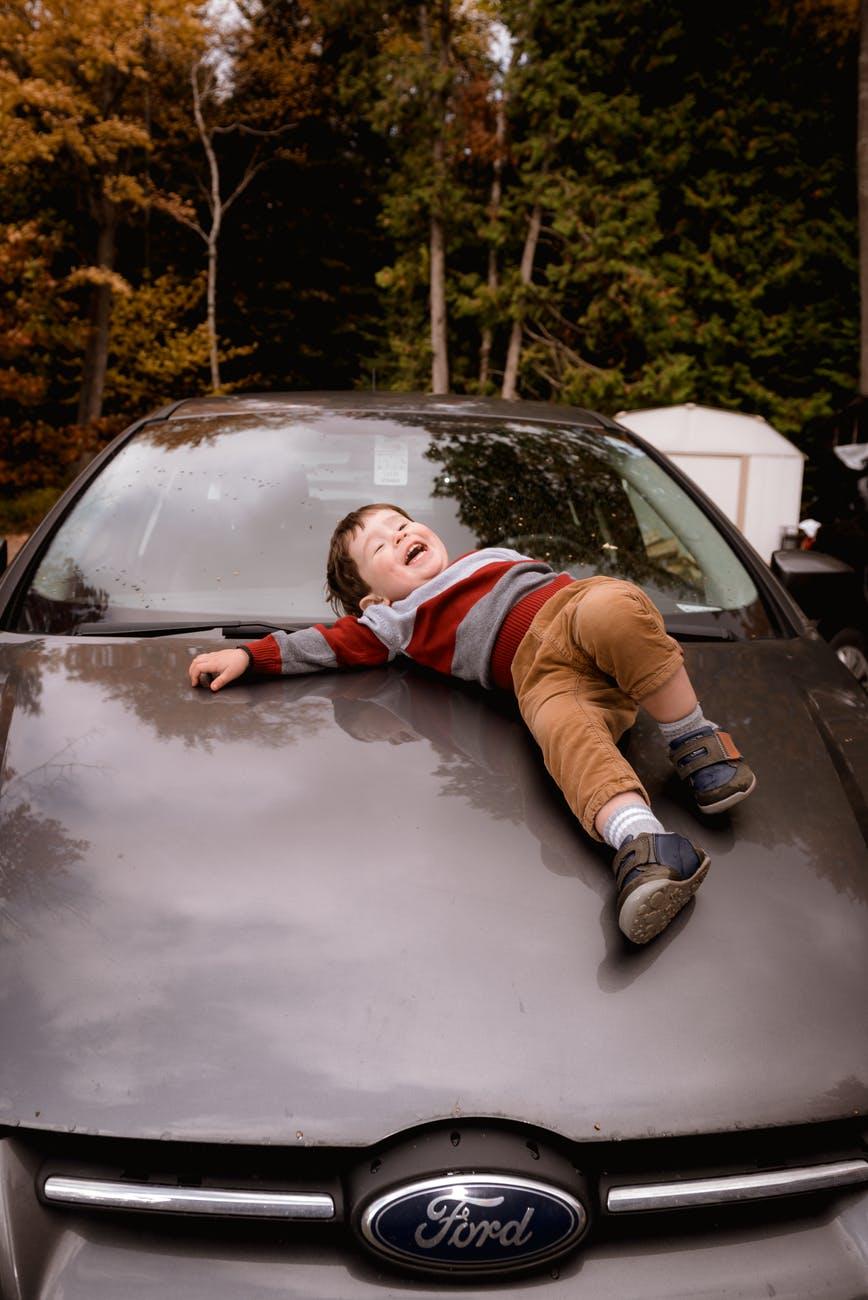photo of boy lying down on car hood