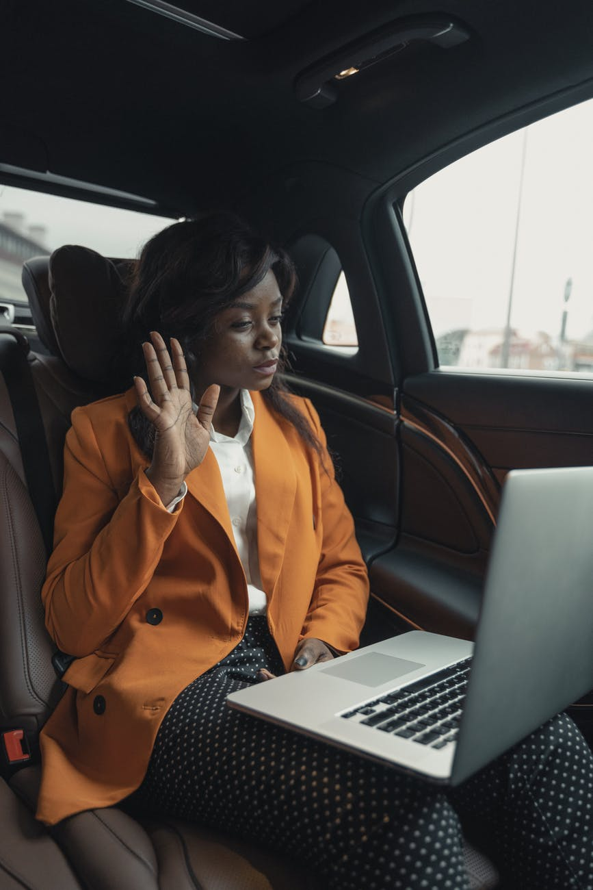 woman in orange blazer sitting inside a car
