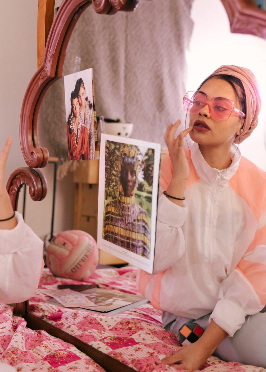 trendy ethnic woman applying lip balm in front of mirror