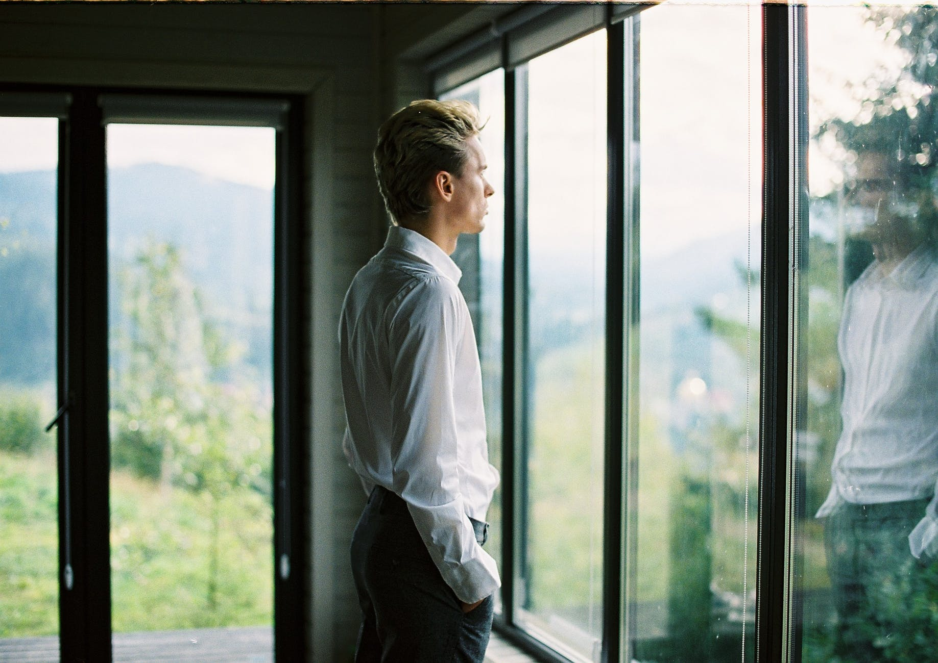 calm well dressed male standing near window at home