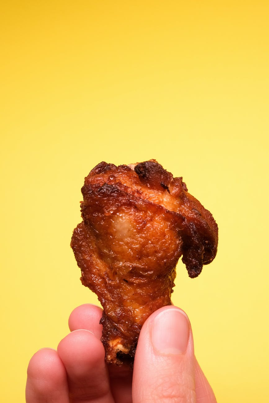 unrecognizable person with fried chicken in fingers