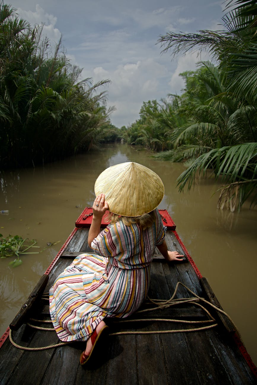 back view of a person wearing coolie hat while sitting on a raft