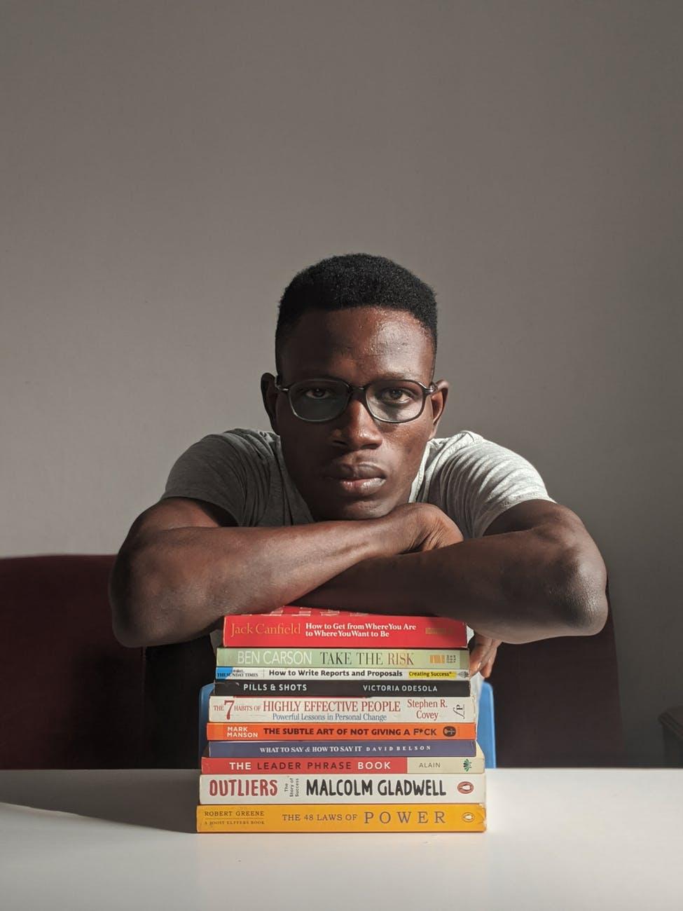 man wearing eyeglasses sitting beside table